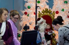 ABINGTON, MA, December 7, 2013 — A young boy sits on Santa Claus' lap inside The Christmas Place, while his mother purchases a photo package. The two were at the head of a winding line of about 25 people.