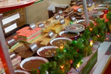 """ABINGTON, MA, December 7, 2013 — Along the side of The Christmas Place sits a """"fudge shop,"""" boasting holiday flavors such as egg nog, peppermint and pumpkin pie. Tables and chairs fill a small café to the fudge shop's left, filled with customers."""