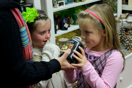 ABINGTON, MA, December 7, 2013 — Hailey Wilson and her sister Colleen, both of Plymouth, MA, take turns sniffing a holiday-scented candle with the help of their grandmother. The candle was one of about 100 lining one of the shop's walls at The Christmas Place.
