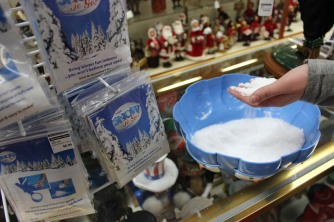 ABINGTON, MA, December 7, 2013 — Meghan Burns of Weymouth, MA, feels a bowl full of artificial snow at The Christmas Place. Being sold for nearly $7, a bag of white fluff needs water to become indoor snow.