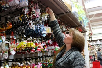 ABINGTON, MA, December 7, 2013 — Elaine Correia of Rockland, MA, reaches for an ornament at The Christmas Place. She and her son (not pictured) Rocco picked out a Grinch ornament together.