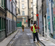 A worker paints over some vibrantly colored street art in downtown Dublin.