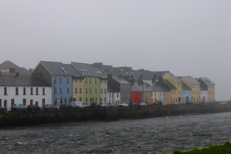 A row of colorful houses in Galway sits near the river.