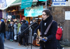 Shoppers and merchants alike watched this guitarist play songs all afternoon.