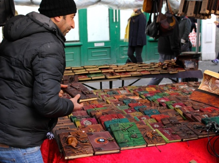 A merchant rearranging leather journals at his stand at the Portobello Road Market.