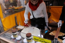 Here, a crepe-maker is bundled up against the cold, spreading out crepe mix on her stovetop.