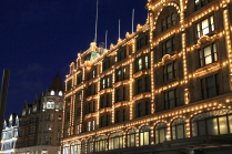 The outside of Harrods, London's very own famous department store, which is lit up at night.