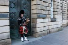One of Edinburgh's many pipers, checking his phone between songs.