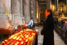 A man praying inside a Lisbon church after lighting a candle.