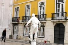 A man doing a street performance near the arch.